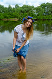 Young woman on river bank squeezes wet hem of skirt Stock Image