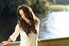 Young Woman at River. Casually dressed brunette relaxes next to river Stock Image