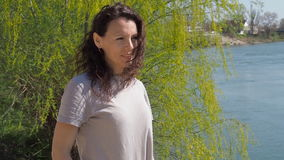 Young woman by the river. Girl at the water with developing hair. A spring sunny day. stock footage