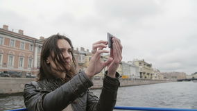 Young woman on a river tour, taking photos, using smartphone. Wind blows hair. City view of St Petersburg. Slow mo stock footage