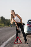 Young woman on the road. Blonde girl with suitcase on the road Stock Photography