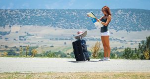 Young woman on the road with baggage and map Stock Image