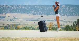 Young woman on the road with baggage Stock Images