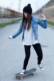 Young woman on the road with a skateboard Royalty Free Stock Image