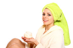 Young woman in a robe and with a towel on her head holding a jar Stock Photo