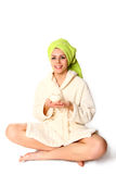 Young woman in a robe and with a towel sitting and holding a jar Stock Images