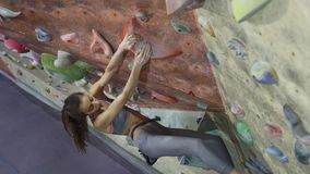 Young woman rock climber is climbing a bouldering at indoor climbing gym. Slim pretty woman making some hard moves and stock footage