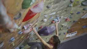 Young Woman Rock climber is Climbing a bouldering At Indoor climbing Gym. slim pretty Woman making some hard moves and stock video