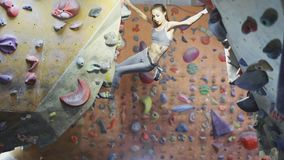 Young woman rock climber is climbing a bouldering at indoor climbing gym. Slim pretty woman making some hard moves and stock video footage
