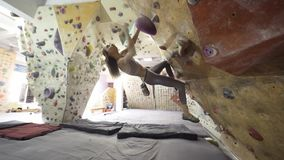 Young Woman Rock climber is Climbing At Inside climbing Gym. slim pretty Woman Exercising At Indoor Climbing Gym Wall stock video footage