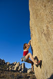 Young woman rock climbing. Stock Images