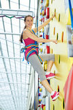 Young woman on rock-climbing wall Royalty Free Stock Image