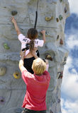 Young woman on rock wall. Young lady rock climbing royalty free stock images