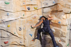 Young woman on rock wall Stock Image