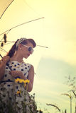 Young woman with a rockabilly outfit and a sunshade in a meadow Stock Photography