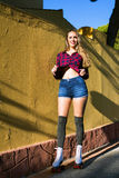 Young woman in roller skates leaning on wall and posing Stock Photo