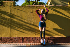 Young woman in roller skates leaning on wall and posing Stock Photos