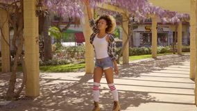 Young woman roller skating down an arcade. Under a colorful flowering purple wisteria on a trellis stock video