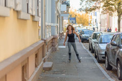 Young woman roller skating down an urban street Stock Photography