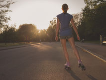 Young woman roller skating in park at sunset Royalty Free Stock Photo