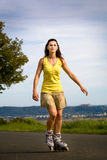 Young woman on rollerblades in the country Royalty Free Stock Photo