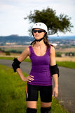 Young woman on rollerblades in the country Stock Image