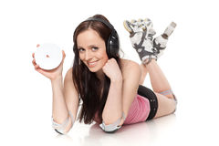 Young woman in rollerskates with earphones and CD. Royalty Free Stock Image