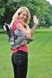 Young woman with rollerskates giving good bye. Young smiling woman with rollerskates giving good bye gesture with hand. Outdoors in park Stock Photos
