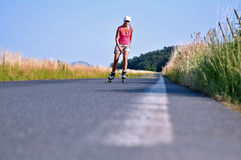 Young woman rollerskating. On the road Royalty Free Stock Photos