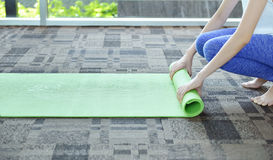 Young woman rolling mat after a yoga on carpet floor, Yoga conce Royalty Free Stock Photos