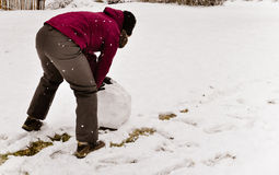 Young woman rolling snowball Stock Image