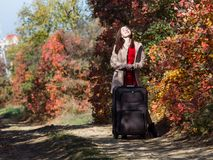 Young woman with rolling suitcase on country road in the forest. Female person in red dress and coat walking along autumn trees stock image