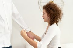 Young woman rolling up her boyfriend sleeves stock image