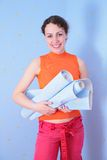 Young  woman with rolls of wall-paper Royalty Free Stock Photos