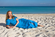 Young woman in a romantic dress lies on sand near the sea, Cuba, Varadero Stock Photography
