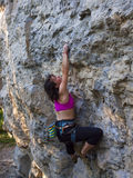 Young woman with rope climbs on the rock. Stock Photography