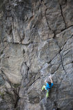 Young woman with rope climbs on the rock. Royalty Free Stock Photography