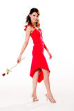 Young woman with a rose. Young woman in a dance like pose wit a rose in her hand Royalty Free Stock Image