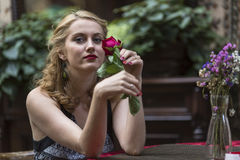 Young  woman with rose in hands sitting at a table in outdoors cafe. Stock Images