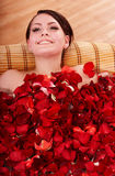 Young woman in rose petal swim water. Royalty Free Stock Photos