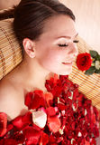 Young woman in rose petal swim water. Beautiful young woman in rose petal swim water. Beauty spa stock photo