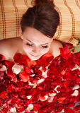 Young woman in rose petal swim water. Stock Image