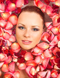 Young woman in rose petal swim water Stock Images