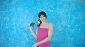 Young woman with a rose smiles on a pastel background stock footage