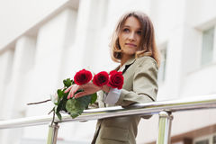 Happy fashion woman with a red roses on city street Royalty Free Stock Photography