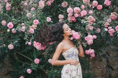 Young woman among roses in a garden. Beautiful young woman with long curly hair among roses in a garden Stock Images