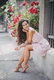 Young woman among roses in a garden. Girl with beautiful curly hair wearing pink dress among pink and red roses Stock Photography