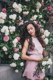 Young woman among roses in a garden. Girl with beautiful curly hair wearing pink dress among pink and red roses Royalty Free Stock Image