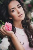 Young woman among roses in a garden. Girl with beautiful curly hair wearing pink dress among pink and red roses Royalty Free Stock Photography