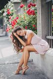 Young woman among roses in a garden. Girl with beautiful curly hair wearing pink dress among pink and red roses Stock Photo